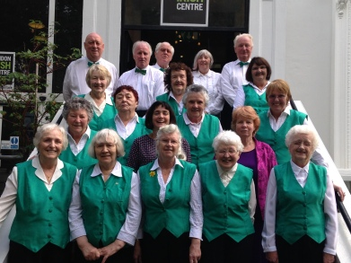 Irish Pensioners' Choir with their new choir leader Natasha Lohan and Director if the Irish Elderly Advice Network Sally Mulready, on the steps of the London Irish Centre